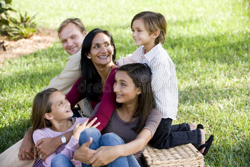Familia interracial feliz de cinco que disfruta de una comida campestre imagen de archivo libre de regalías