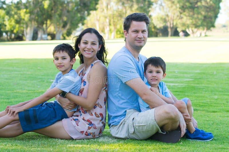 Familia interracial joven relajada al aire libre fotos de archivo