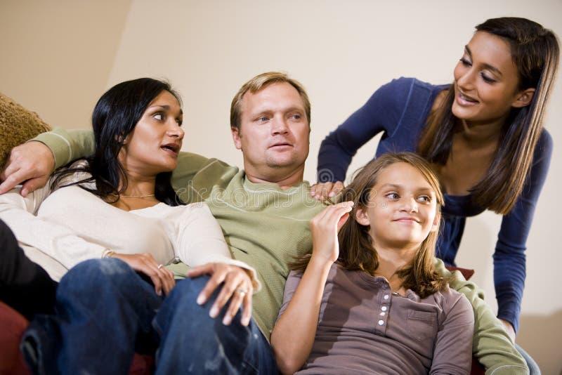Familia interracial que se sienta junto en el sofá foto de archivo libre de regalías