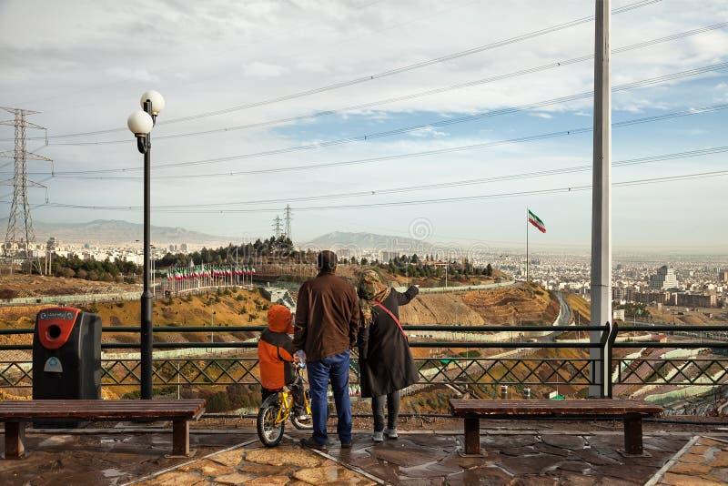 Familia iraní con su hijo en la bicicleta que mira fijamente el horizonte de Teherán de un parque de la tierra alta imágenes de archivo libres de regalías