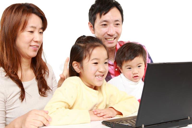 Familia japonesa en el ordenador portátil imagen de archivo