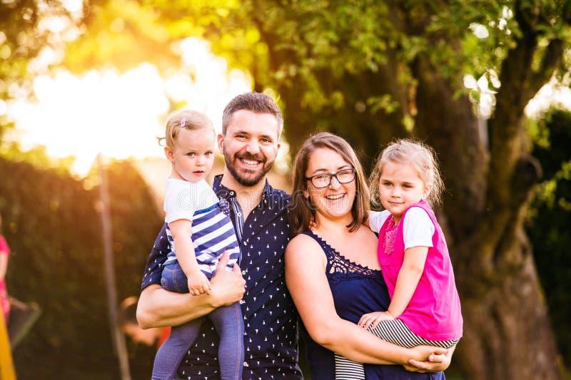 Familia joven afuera en el parque soleado del verano, naturaleza verde imagen de archivo