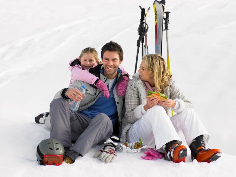 Familia joven con comida campestre el vacaciones del esquí fotos de archivo