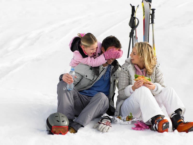 Familia joven con comida campestre el vacaciones del esquí fotografía de archivo