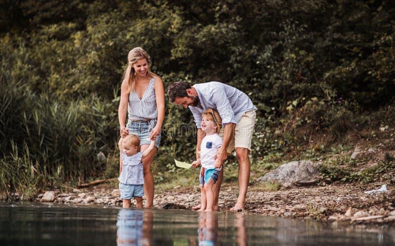 Familia joven con dos niños del niño al aire libre por el río en el verano, jugando fotos de archivo