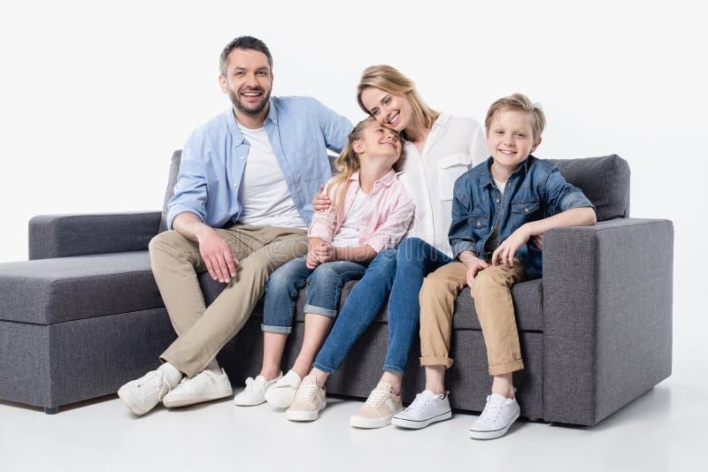 Familia joven con dos niños que se sientan junto en el sofá aislado en blanco fotografía de archivo