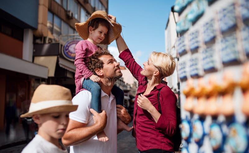 Familia joven con dos pequeños niños que se colocan al aire libre en ciudad el día de fiesta fotografía de archivo libre de regalías