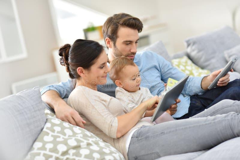 Familia joven con el bebé en casa usando la tableta foto de archivo