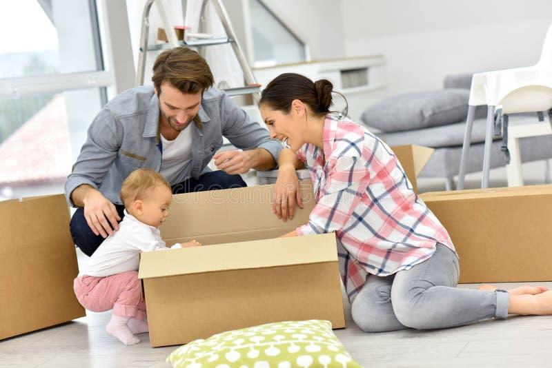 Familia joven con el bebé que desempaqueta las cajas que se trasladan a nueva casa fotos de archivo libres de regalías