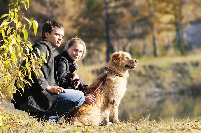Familia joven con el perro imagenes de archivo