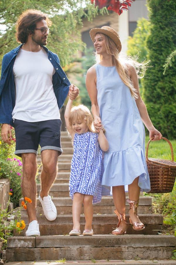 Familia joven con la cesta después de la comida campestre que camina abajo de las escaleras afuera en parque verde imagen de archivo