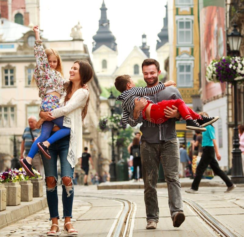 Familia joven con la ciudad turística vieja de la calle de dos niños que camina imagen de archivo libre de regalías