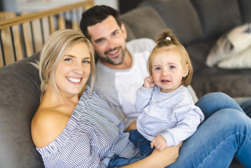 Familia joven con la hija del bebé en el sofá en casa, el griterío del bebé fotografía de archivo libre de regalías