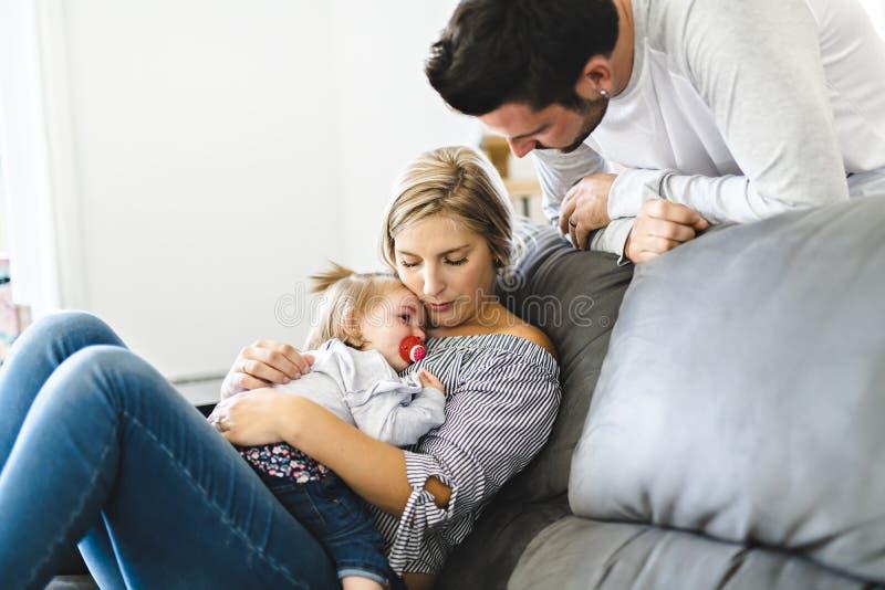 Familia joven con la hija del bebé en el sofá en casa, el griterío del bebé imagenes de archivo