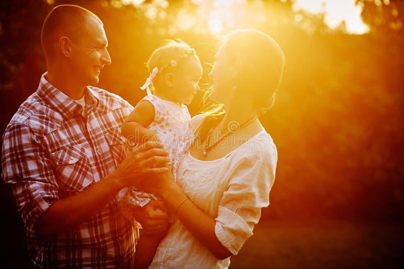 Familia joven con la pequeña hija que camina en el parque en la puesta del sol imagen de archivo