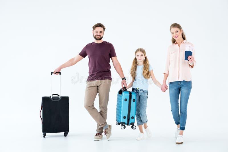 Familia joven con los bolsos de los pasaportes, de los boletos y el viajar foto de archivo