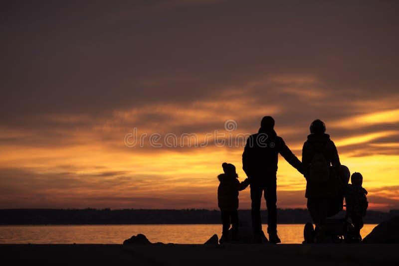 Familia joven con los niños que llevan a cabo las manos imágenes de archivo libres de regalías