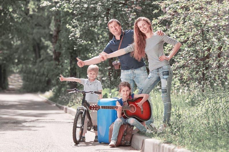 Familia joven con los ni?os, viajando haciendo autostop imagen de archivo