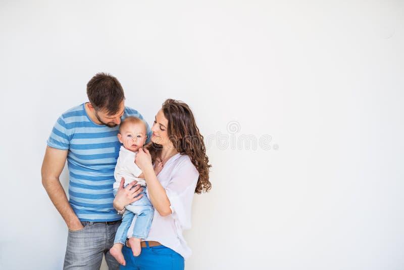 Familia joven con un bebé en casa, colocándose y presentando para la foto imagen de archivo libre de regalías