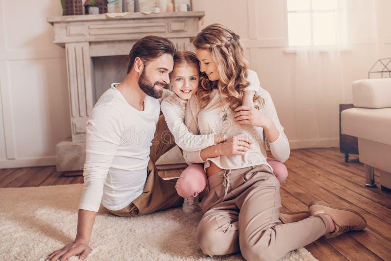 Familia joven con un niño que se sienta en la alfombra y que abraza en casa fotografía de archivo libre de regalías
