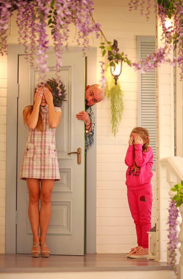 Familia joven de la diversión que juega escondite en casa fotos de archivo libres de regalías