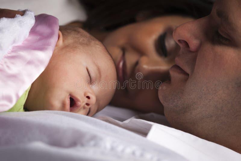 Familia joven de la raza mixta con el bebé recién nacido foto de archivo