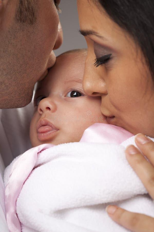 Familia joven de la raza mixta con el bebé recién nacido foto de archivo libre de regalías