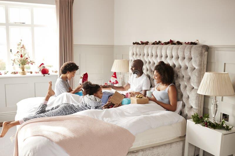 Familia joven de la raza mixta en la cama del ½ s del ¿del parentï que se da los regalos el la mañana de la Navidad, vista latera imagen de archivo