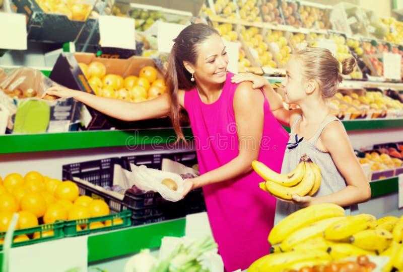 Familia joven de mujer y de hija que compran diversas frutas fotografía de archivo libre de regalías
