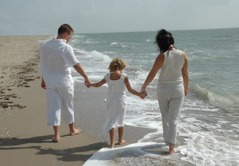 Familia joven en la playa fotos de archivo
