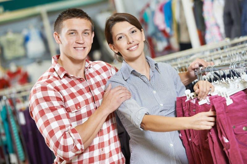 Familia joven en la tienda que hace compras de la ropa foto de archivo