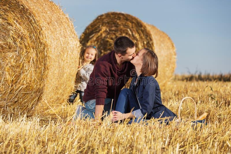Familia joven feliz con la muchacha de 2 años al lado de las balas de heno imagenes de archivo