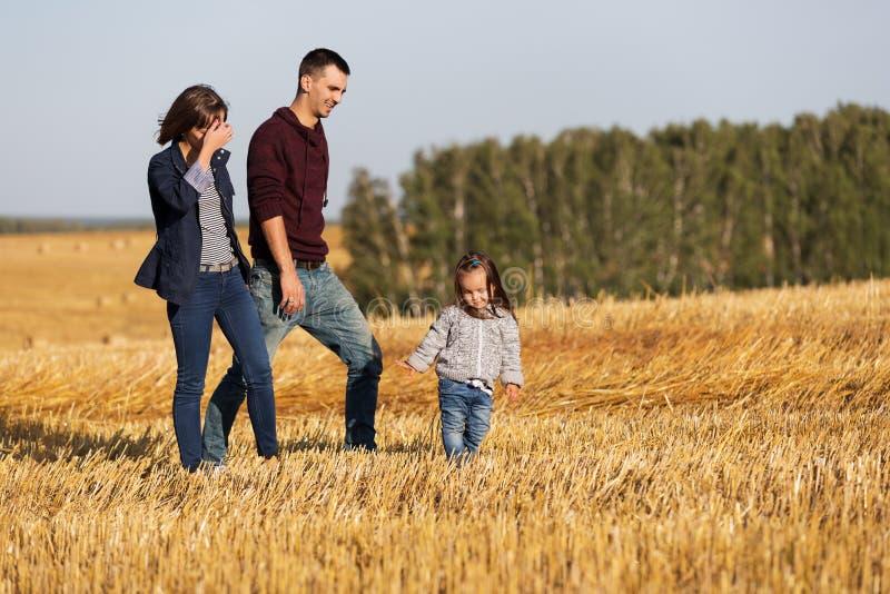 Familia joven feliz con la muchacha de dos años que camina en campo cosechado fotos de archivo