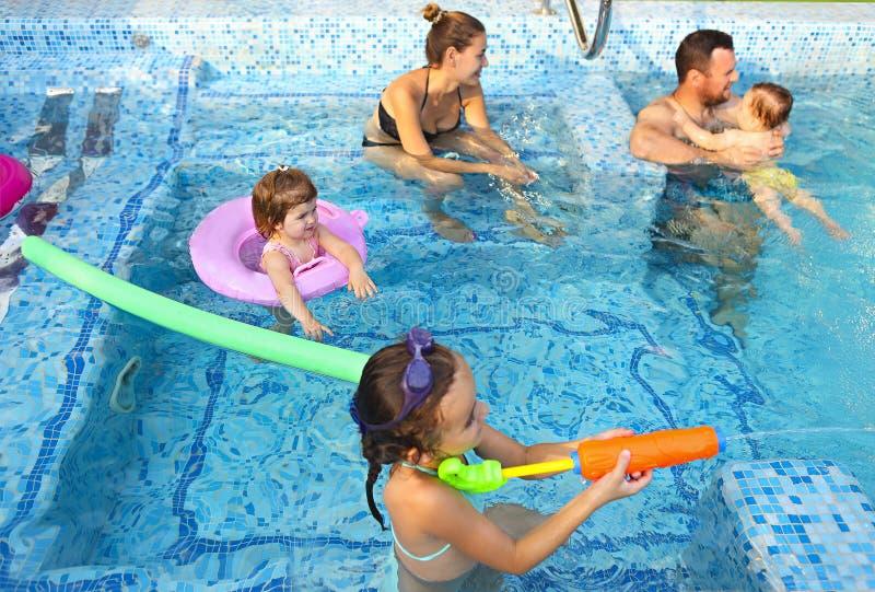 Familia joven feliz con los niños en la piscina imagenes de archivo