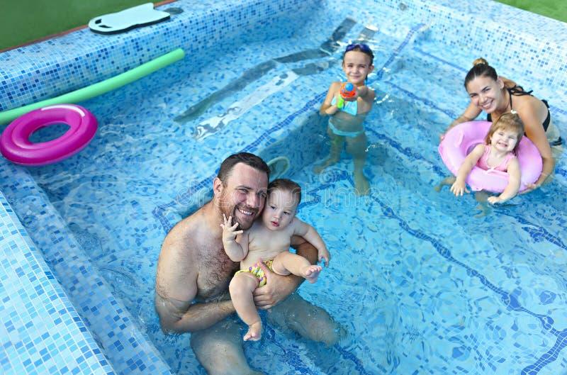 Familia joven feliz con los niños en la piscina imagen de archivo