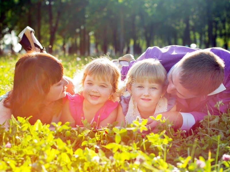 Familia joven feliz con los niños que mienten en la hierba foto de archivo