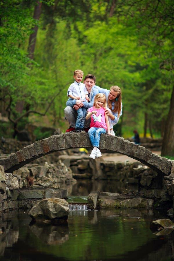 Familia joven feliz con los ni?os en parque verde del verano en el puente de piedra sobre el r?o en bosque imagenes de archivo