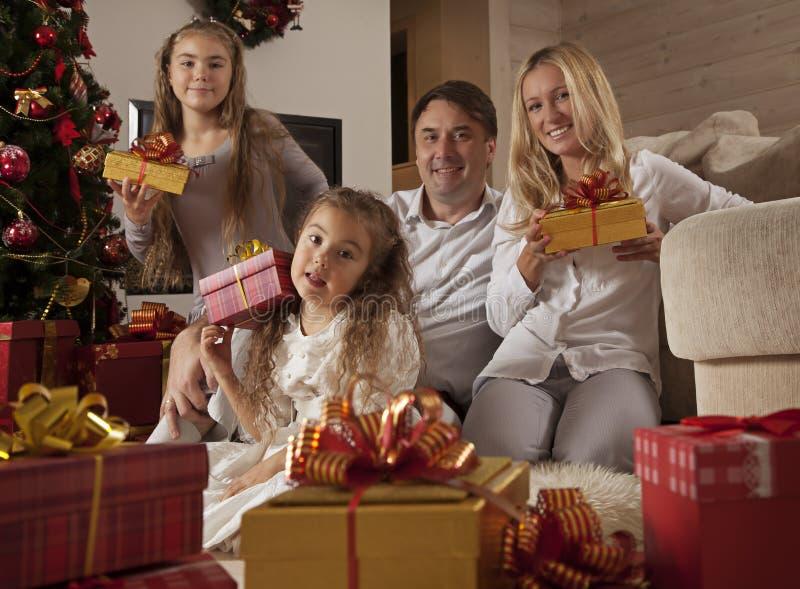 Familia joven feliz con los regalos de la Navidad imagen de archivo