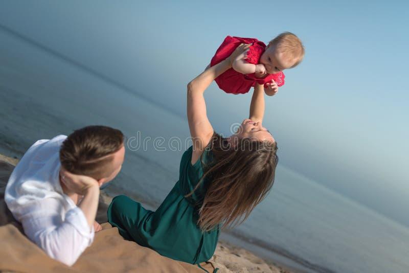 Familia joven feliz con poco niño, divirtiéndose en la playa fotos de archivo libres de regalías