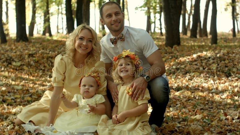 Familia joven feliz con sus niños que pasan el tiempo al aire libre en el parque del otoño imágenes de archivo libres de regalías