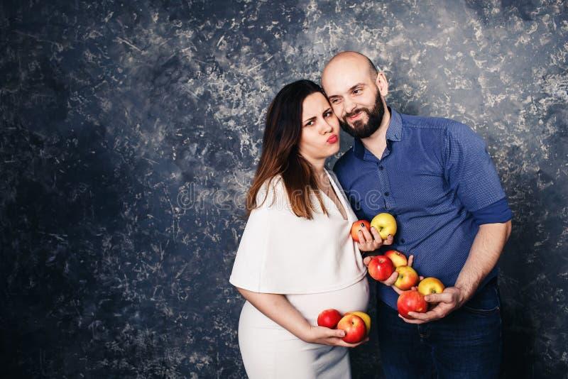 Familia joven feliz del vegano una muchacha embarazada y un hombre barbudo que sostienen manzanas en sus manos y que hacen caras  fotos de archivo libres de regalías