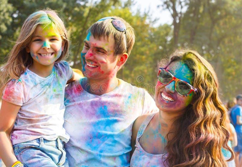 Familia joven feliz en festival del color del holi foto de archivo