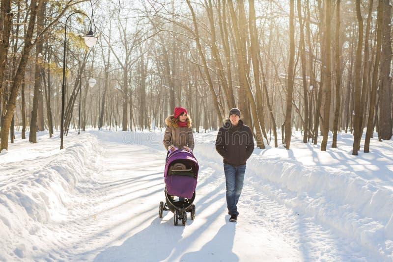 Familia joven feliz que camina en el parque en invierno Los padres llevan al bebé en un cochecito a través de la nieve fotos de archivo