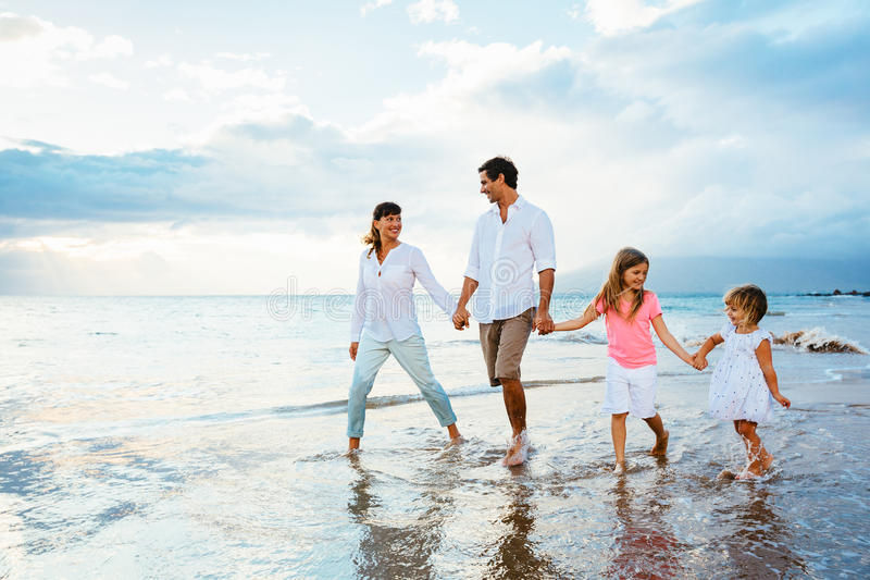 Familia joven feliz que camina en la playa fotos de archivo libres de regalías