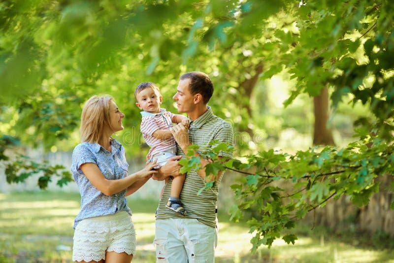 Familia joven feliz que camina en parque del verano fotografía de archivo libre de regalías