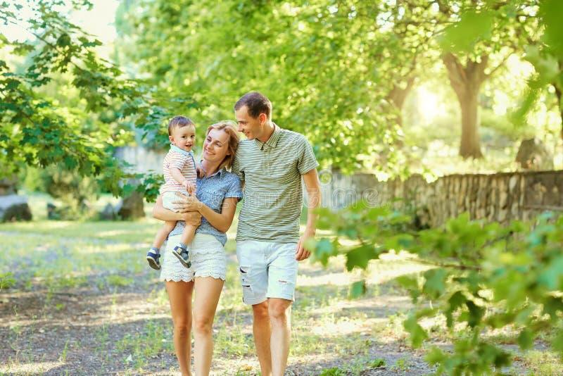 Familia joven feliz que camina en parque del verano imagen de archivo libre de regalías