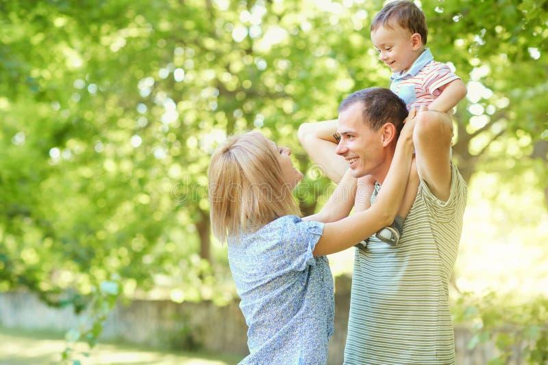 Familia joven feliz que camina en parque del verano imagen de archivo