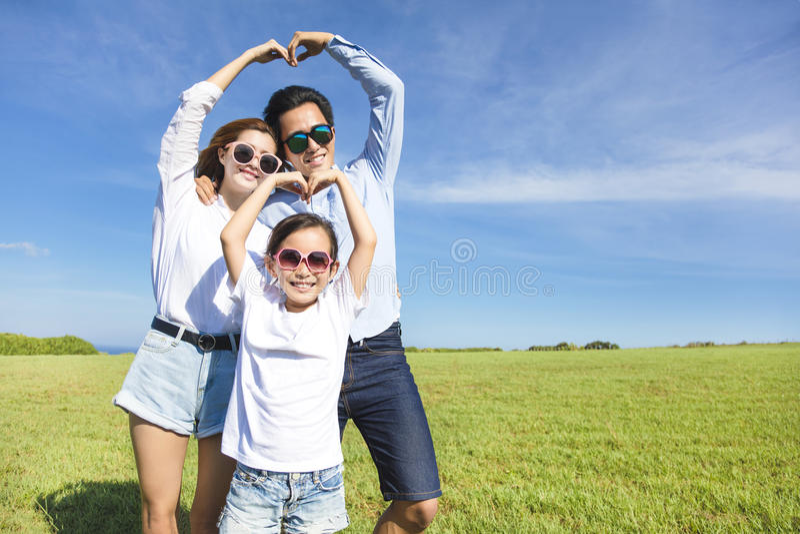 Familia joven feliz que forma forma del amor foto de archivo