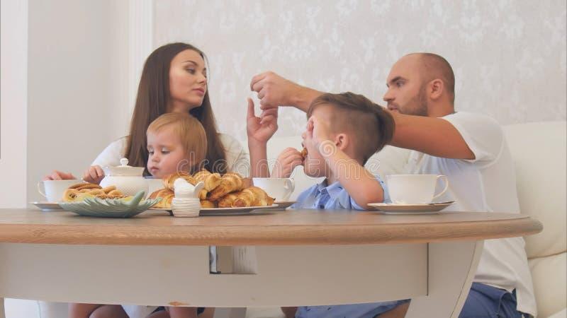 Familia joven feliz que goza de té con los dulces en el restaurante o café u hogar foto de archivo