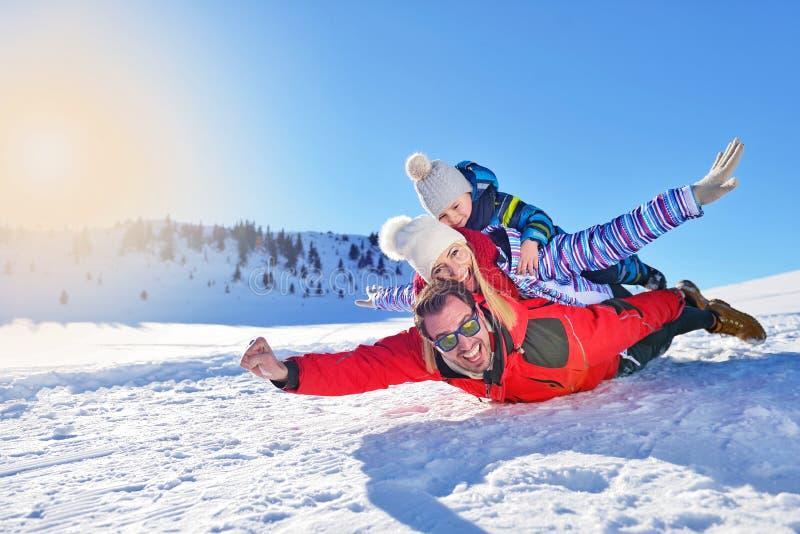 Familia joven feliz que juega en nieve fresca en el día de invierno soleado hermoso al aire libre en naturaleza fotos de archivo libres de regalías
